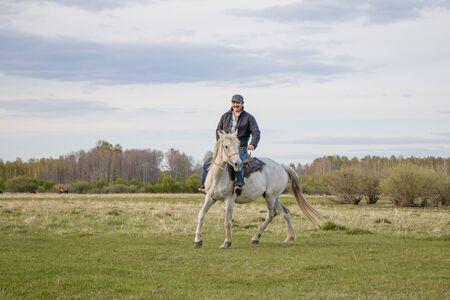 A rider on a white horse in the field Foto de archivo - 127676551