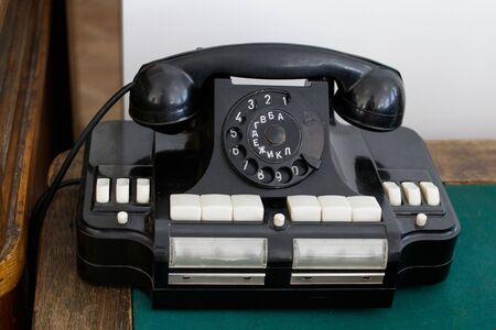 Old Soviet office phone with Russian letters on a wooden table, the tabletop is covered with green fabric. Banque d'images
