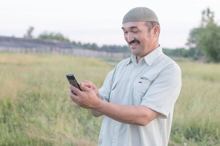Muslim senior man uses a mobile phone in a Siberian village
