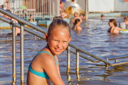 Portrait of a cute little smiling girl sitting in a thermal pool
