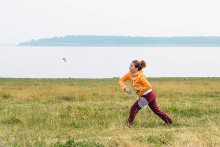 Beautiful girl in bright sportswear plays badminton on coast of lake.