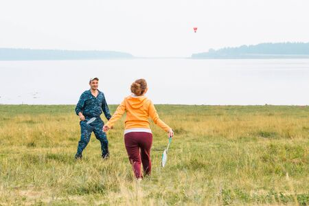 Young couple play badminton on the lake. The guy gave the pitch. The girl is preparing to hit the shuttlecock with a racket.