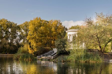 Old park in the fall. View of the lake and the white rotunda.