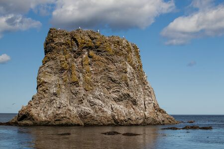 A beautiful rock formation off the coast of the Sea of Okhotsk, on the top of which gulls live. Cape Velikan, Sakhalin Island, Russia.