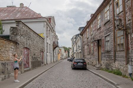 Paved with cobblestone street of the old town with an spectacular ancient abandoned wooden two-story house.
