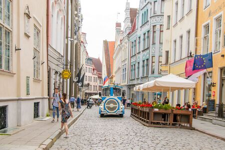 A funny blue tourist bus rides along the street of the Old Town of Tallinn