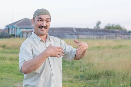 Muslim senior man stands and talks about something funny against the background of a Siberian village, Russia