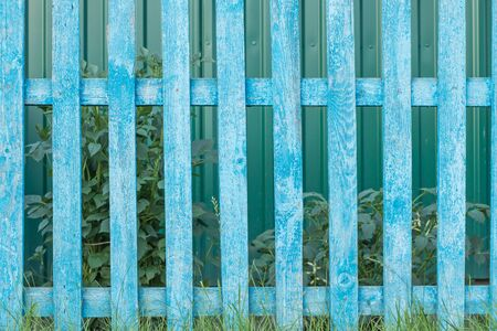 Old rustic wooden fence with shabby blue paint as background
