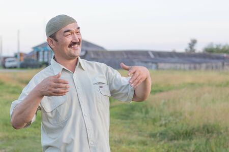 Muslim senior man stands and smiles on the background of the Siberian village, Russia
