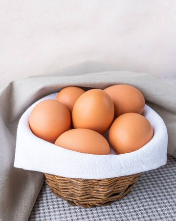Brown fresh raw eggs lie on a white napkin in a small rough rustic basket. The basket is on the table on a beige background. Copy space Place for text Vertical Banque d'images - 138555110