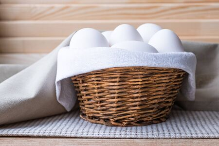 White fresh raw eggs lie on a white napkin in a small rough rustic basket. The basket is on the table on a wood background. Copy space Close up Banque d'images - 138555109
