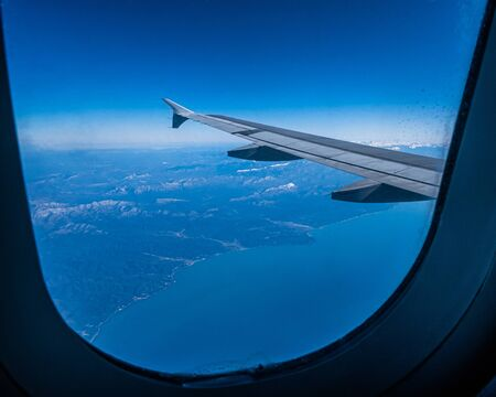 View of the wing of an airplane flying over the mountains and the sea