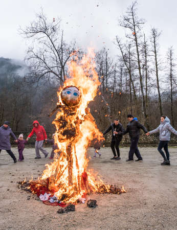Sochi, Russia - March 1, 2020: Rite of burning a stuffed Pancake week. East Slavic traditional holiday containing elements of Slavic mythology. People are dancing around the fire.