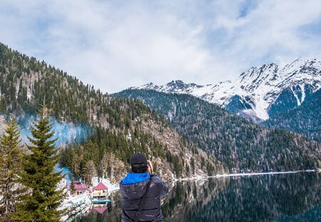 A man in a black jacket with a blue hood takes a picture of a beautiful winter landscape of the Caucasus mountains and Lake Ritsa, located in Abkhazia