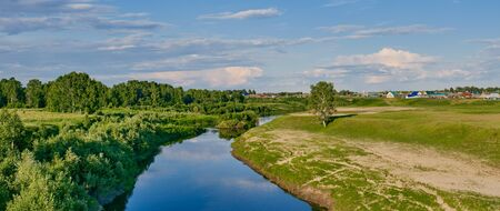 Summer landscape on a sunny day. Neighborhood of the Siberian village Begitino, Tyumen region, Russia. Vagai river, lonely birch and taiga forest standing on a meadow. Beautiful clouds in the sky. 스톡 콘텐츠 - 149524135