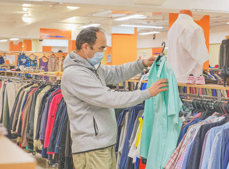 Mature man in mask choosing clothes at Second hand store. Conscious consumption, a new normal concept Reklamní fotografie