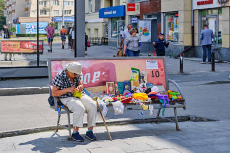 Yekaterinburg, Russia - July 29, 2020: An elderly woman sits on a street bench and knits. Next to her are knitwear and old books that she sells.