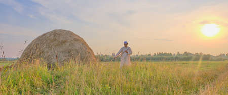 At sunset an senior Muslim man in an embroidered skullcap and white traditional Clothes mows hand-scythe grass in a hayfield. Country life concept