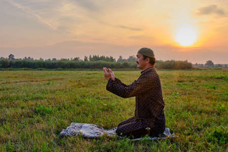 A Muslim senior man wearing a skullcap and traditional clothes prays at sunset in a field Stock Photo