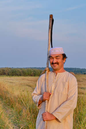 Portrait of smiling senior muslim man in an embroidered skullcap and white traditional clothes with hand-scythe in a hayfield. Looking at the camera. Country life concept
