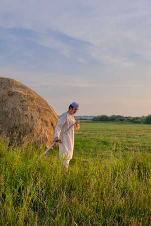 An senior Muslim man in an embroidered skullcap and white traditional Clothes mows hand-scythe grass in a hayfield. Country life concept