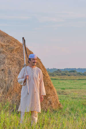 An senior Muslim man in a skullcap and traditional clothes leaves with a hand scythe from the hay field at sunset. Country life concept Stock Photo