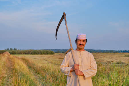 Portrait of senior asian man in an embroidered skullcap and white traditional clothes with hand-scythe in a hayfield. Looking at the camera. Country life concept