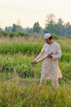 An senior asian man in an embroidered skullcap and white traditional clothes mows hand-scythe grass in a hayfield. Country life concept