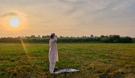 A Muslim senior man wearing an embroidered skullcap and white traditional clothes prays at sunset in a field Banner Stock Photo