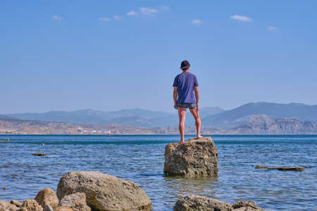 Senior asian man in shorts, t-shirt and baseball cap, holding in his hand in face mask, stands alone on a stone in a sea bay over a background of mountains Stock fotó - 155450157