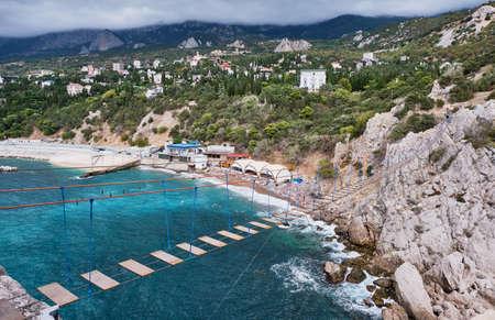 Suspension bridge to the Diva rock, Black Sea coast, near Yalta, Crimea. Panorama of the town of Simeiz.