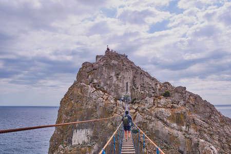 A middle-aged man with a backpack walks over a suspension bridge to Diva Rock, Black Sea coast, near Yalta, Crimea.