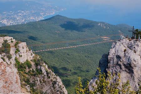 Beautiful mountain landscape of the southern Crimea. Ai Petri plateau. Suspension bridge between mountain battlements for extreme entertainment.