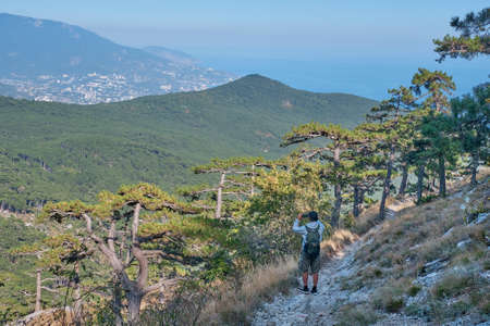 Beautiful landscape of the southern Crimea. Scenic slope of Ai Petri mountain. A man with a backpack is walking along the rocky mountain trail and taking a pictures by a smartphone.
