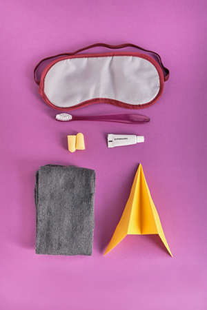 Yellow paper plane and travel kit for comfortable flying on board an airplane on a colored background. Sleep mask, earplugs, small tube of toothpaste, toothbrush, socks. Flat lay. Top view.