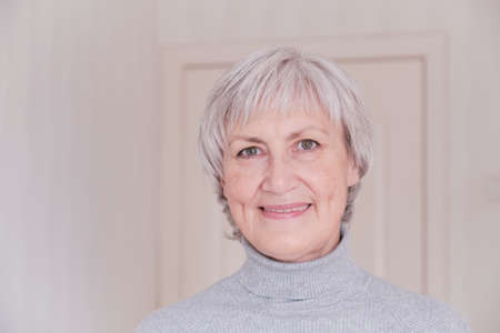 A close-up portrait of a smiling and looking at the camera elderly Caucasian woman with short gray hair on a light background. Stock Photo