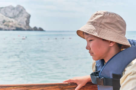 An Asian boy in life jacket floating on pleasure boat on the sea and feeling nauseous. Stockfoto
