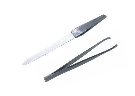 Black metal eyebrow tweezers. Black metal nail file. Female accessories for manicure and personal care isolated on white.