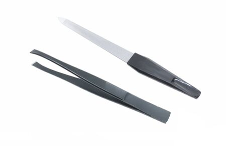 Black metal nail file. Black metal eyebrow tweezers. Female accessories for manicure and personal care isolated on white. Imagens