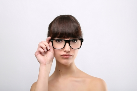 Funny expression. A beautiful woman with a funny expression wearing glasses on a pink background. photo