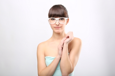 funny glasses: Funny expression. A beautiful woman with a funny expression wearing glasses on a pink background.