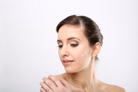 humidify: Fresh beautiful young adult woman applying moisturiser cream on her face