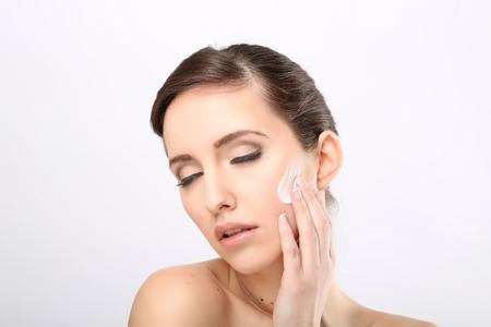 humidify: Fresh beautiful young adult woman applying moisturiser cream on her face