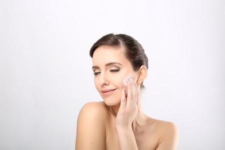 moisturiser: Fresh beautiful young adult woman applying moisturiser cream on her face