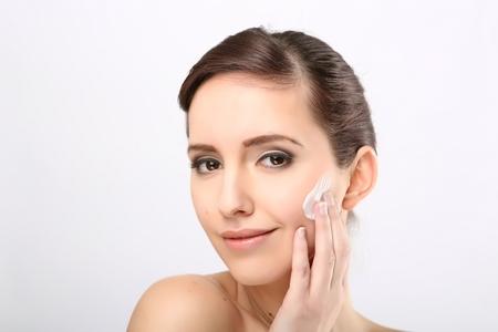 woman face cream: Fresh beautiful young adult woman applying moisturiser cream on her face