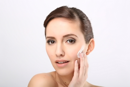 putting up: Fresh beautiful young adult woman applying moisturiser cream on her face