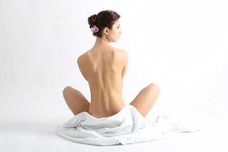 mujer desnuda de espalda: Retrato de una bella dama tapándose con una toalla blanca, aislado en blanco Foto de archivo