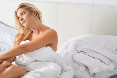 one sheet: Smiling woman under a duvet in her bedroom