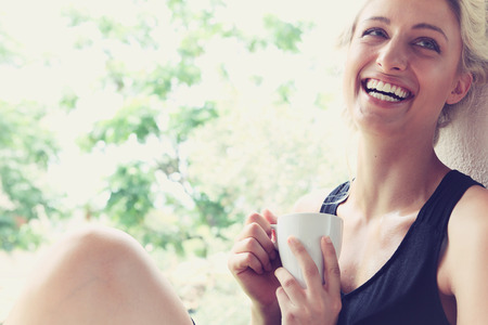 eyes close up: Pretty woman enjoying her morning coffee on a veranda Stock Photo