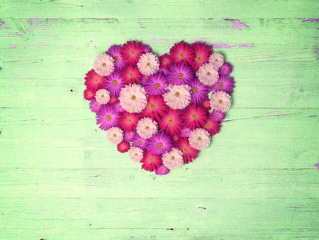 floral grunge: vintage heart from flowers   on wooden table, vintage valentin day background